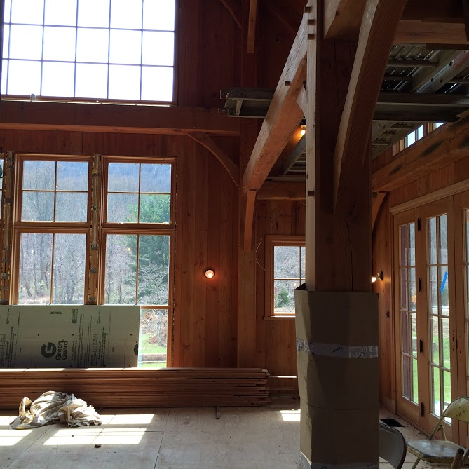 Installed reclaimed building materials that include reclaimed flowing, reclaimed stone, reclaimed logs, reclaimed beams by the Housewright Shop