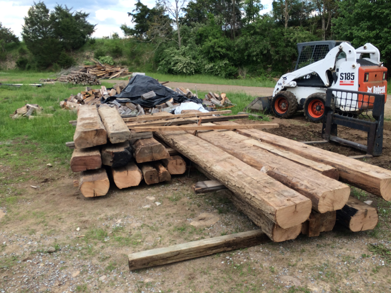 The Housewright Shop stacked reclaimed beams and logs from a recent project